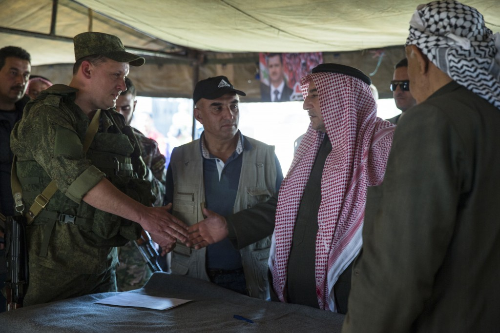 Sheikh Ahmad Mubarak, second from right, shakes hands with a Russian military officer after signing a cease-fire declaration in Maarzaf, Syria, on Wednesday. (AP Photo/Pavel Golovkin, File)