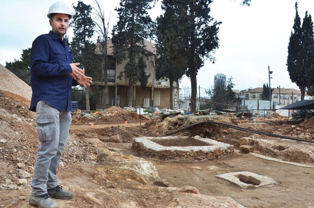 Excavation director, Alex Wiegmann alongside the winery (Israel Antiquities Authority)
