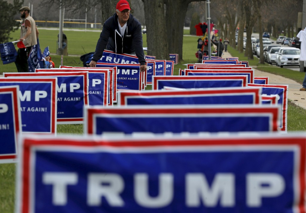Elam Stoltzfus plants lawn signs outside a U.S. Republican presidential candidate Donald Trump campaign rally in West Allis, Wisconsin, United States, April 3, 2016. (Jim Young/Reuters)