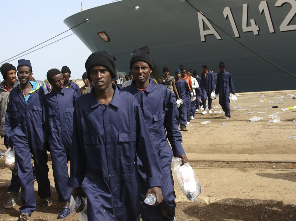 Migrants walk on the dock after disembarking from the German naval vessel Frankfurt Am Main in the Sicilian harbor of Augusta, Italy, on Tuesday. (Reuters/Antonio Parrinello)