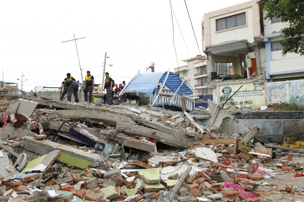 Police officers stand on debris in the Tarqui neighborhood in Manta, Ecuador. (Reuters/Guillermo Granja)