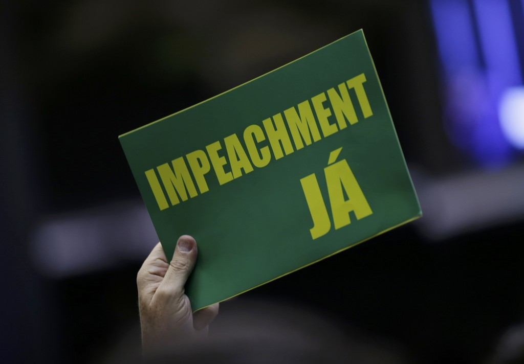 """A member of Brazil's Lower House of Congress in favor of the impeachment of President Dilma Rousseff holds up a sign that reads, """"Impeachment now"""" as representatives voted in Brasilia on Sunday afternoon. (Reuters/Ueslei Marcelino)"""