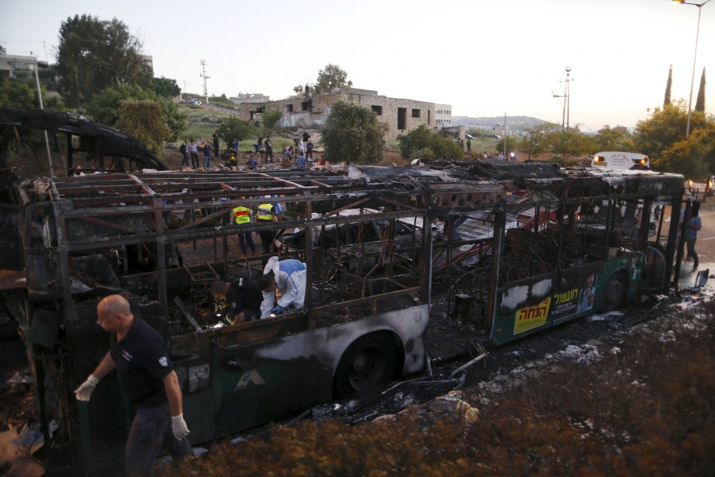 Israeli police forensic experts work at the scene of the bus bombing Monday. (Reuters/Ammar Awad)