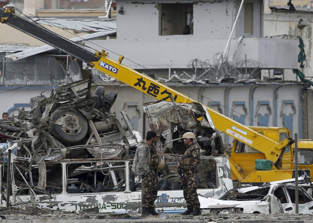 Afghan security forces stand next to damaged vehicles after a blast in Kabul on Tuesday morning. (Reuters/Ahmad Masood)