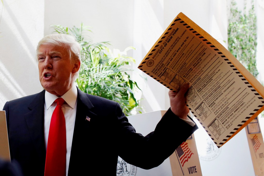 Republican presidential candidate Donald Trump lifts his ballot while voting for the New York primary election in the Manhattan borough of New York City, U.S., April 19, 2016. (Andrew Kelly/Reuters