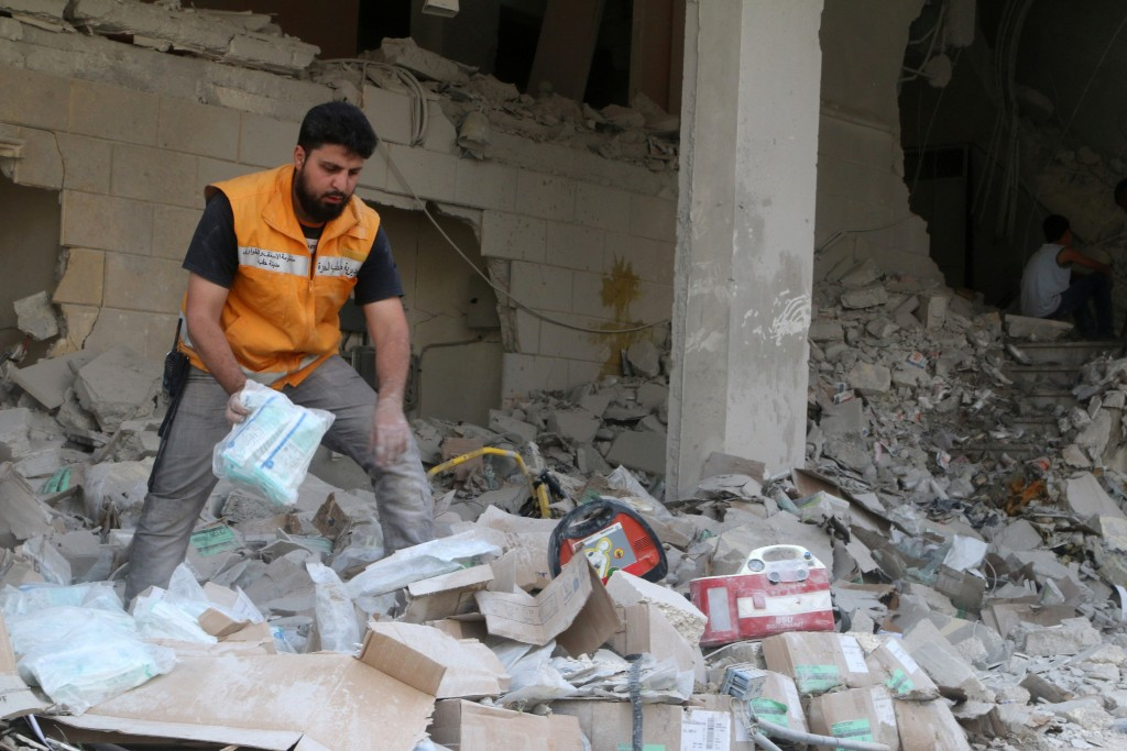 A Red Crescent aid worker inspects scattered medical supplies after an airstrike on a medical depot in the rebel-held Tariq al-Bab neighbourhood of Aleppo, Syria April 30, 2016. REUTERS/Abdalrhman Ismail