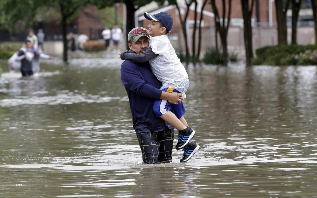 Juan Tadoro carries his son Brandon through floodwaters as they evacuate their home on Monday. (AP Photo/David J. Phillip)