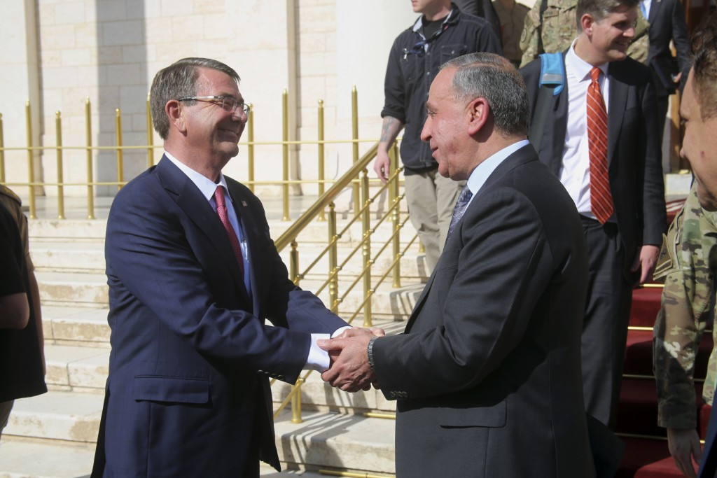 Visiting U.S. Defense Secretary Ash Carter, left, shakes hands with Iraqi Defense Minister Khaled al-Obeidi at the Ministry of Defense in Baghdad on Monday. (AP Photo)