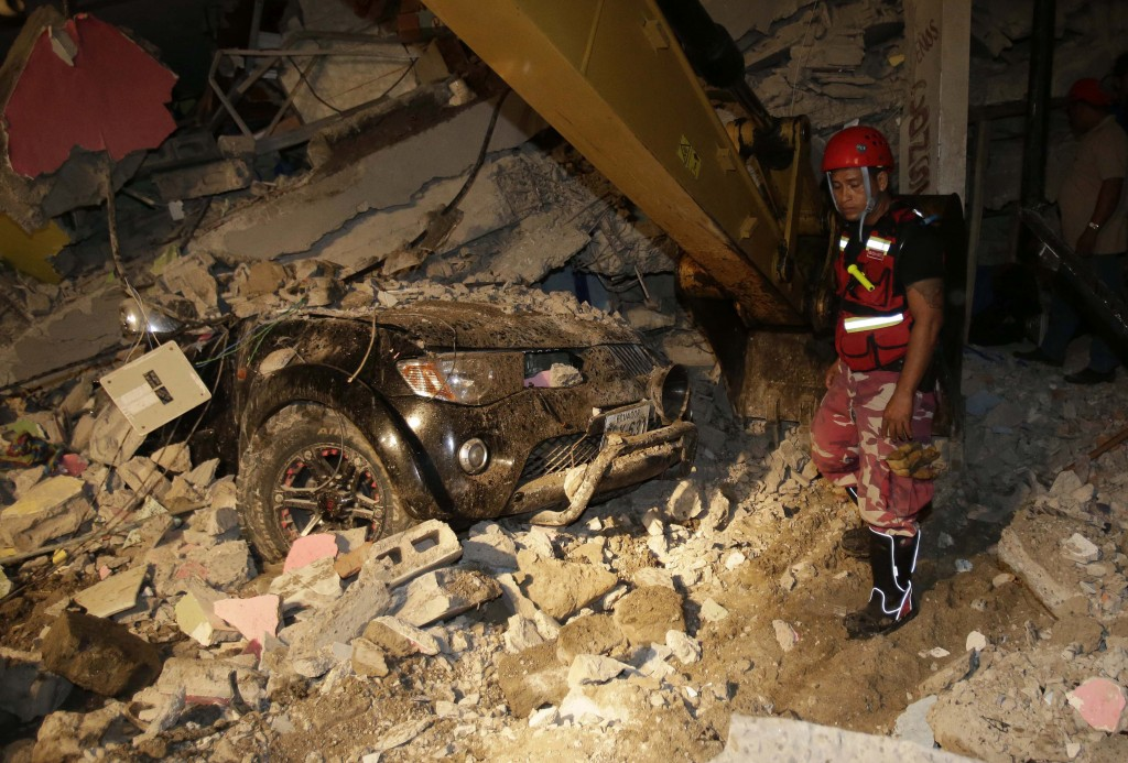 A rescue worker searches in the rubble of a destroyed house in the Pacific coastal town of Pedernales, Ecuador, Sunday, April 17, 2016. The strongest earthquake to hit Ecuador in decades flattened buildings and buckled highways along its Pacific coast, sending the Andean nation into a state of emergency. (AP Photo/Dolores Ochoa)