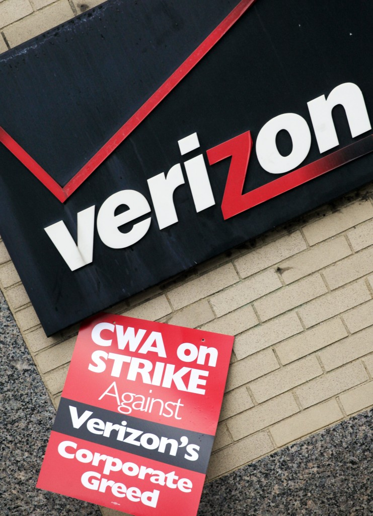 In this Aug 7, 2011 photo, a union strike sign hangs below Verizon's corporate logo in front of a facility in New York. More than 36,000 Verizon landline phone and cable workers are threatening a strike starting Wednesday morning if the company doesn't agree to a new contract.  (AP Photo/Mark Lennihan, File)