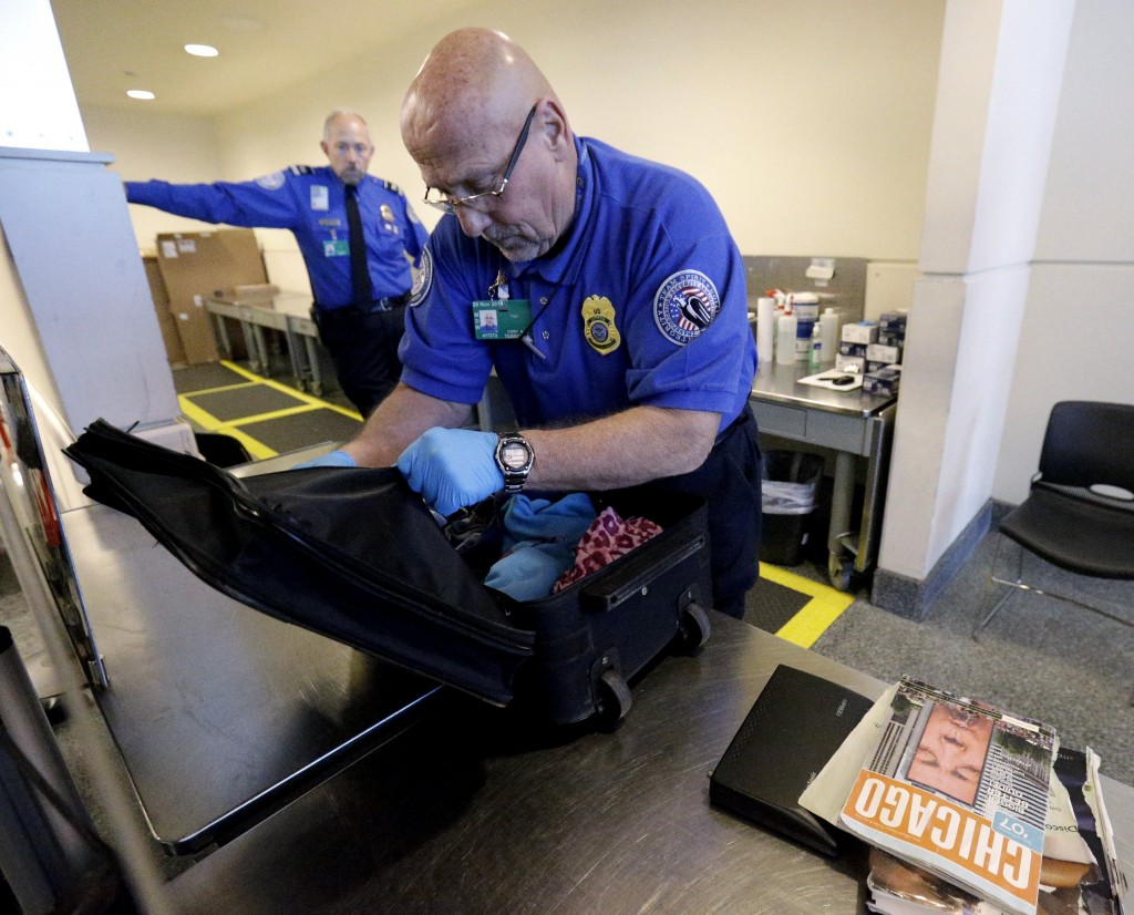 A TSA agent checks a bag at a security checkpoint area at Midway International Airport. (AP Photo/Nam Y. Huh)