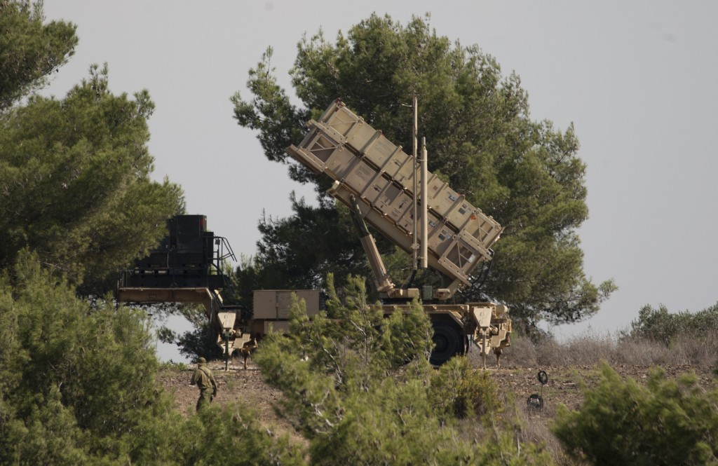 An Israel soldier walks past a Patriot missile defense battery positioned on the Carmel Mt. in northern Israel. (AP Photo/Ariel Schalit)