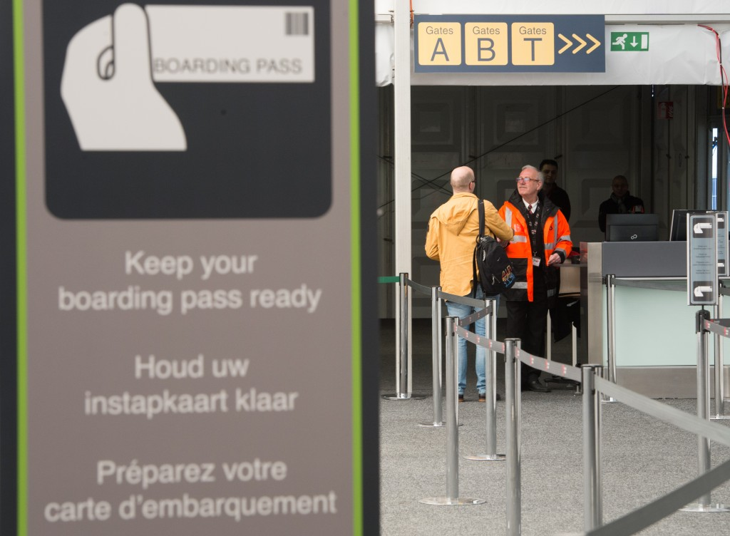 An airport worker helps a passenger at the temporarily check in terminal at Brussels Airport, in Zaventem, Belgium, Sunday, April 3, 2016. Under extra security, three Brussels Airlines flights, the first for Faro in Portugal, were scheduled to leave Sunday from an airport that is used to handling about 600 flights a day. (Benoit Doppagne/Pool Photo via AP)
