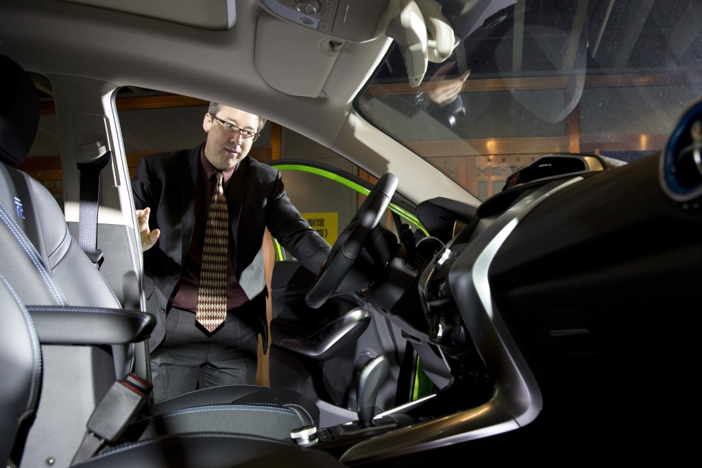 In this photo taken Monday, April 11, 2016, Michael Austin, BYD Co.'s vice president for the United States, looks at the interior of the latest plug in mini-SUV during the BYD Dreams Conference in Beijing, China. The Chinese automaker that sold more electric cars last year than Tesla, Nissan and GM combined is taking a back road into the American market on a battery-powered bus. (AP Photo/Ng Han Guan)