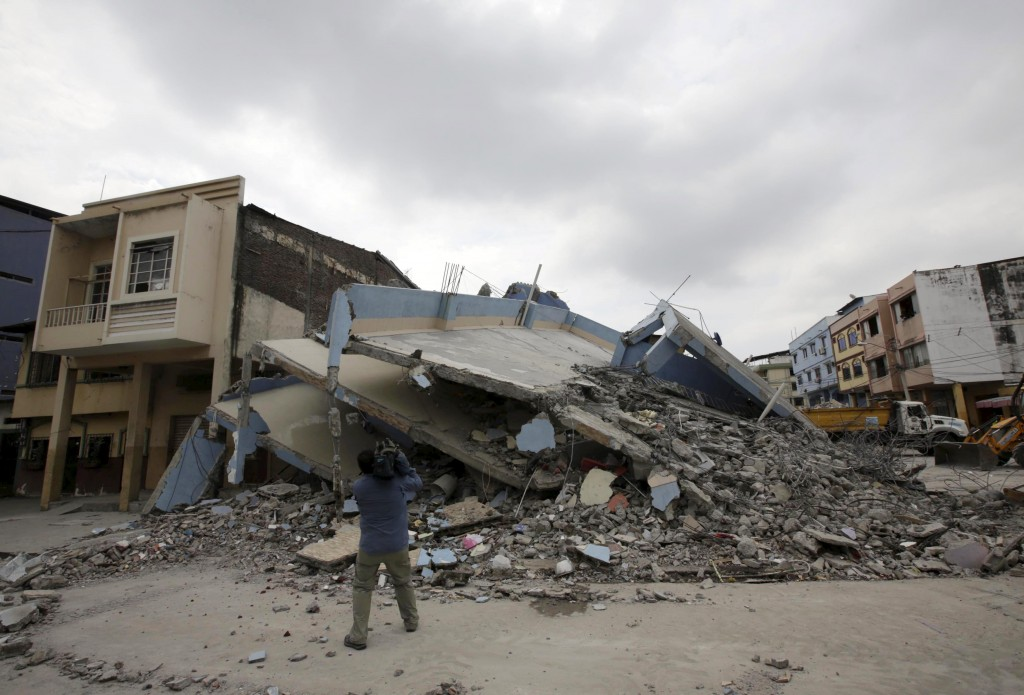 A television cameraman films a collapsed building after an earthquake struck off the Pacific coast, in Guayaquil, Ecuador, April 17, 2016. REUTERS/Henry Romero