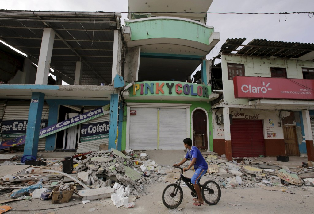 A resident rides his bicycle past collapsed homes in Pedernales, after an earthquake struck off Ecuador's Pacific coast, April 20, 2016. REUTERS/Henry Romero
