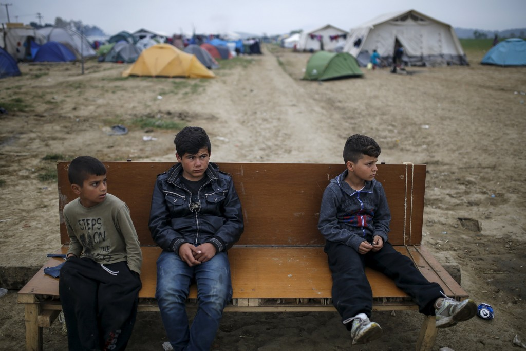 Children sit on a bench at a makeshift camp for migrants and refugees at the Greek-Macedonian border near the village of Idomeni, Greece, April 3, 2016. REUTERS/Marko Djurica TPX IMAGES OF THE DAY
