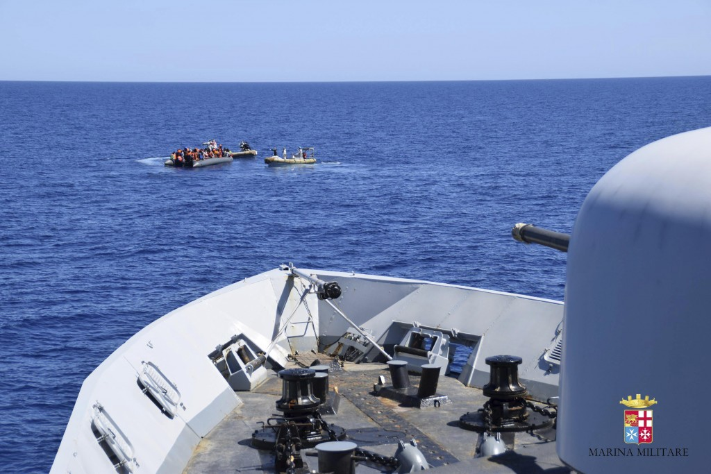 Migrants sit in their boat during a rescue operation by Italian Navy vessels off the coast of Sicily in this April 11, 2016 handout picture provided by Marina Militare. REUTERS/Marina Militare/Handout via Reuters ATTENTION EDITORS - THIS PICTURE WAS PROVIDED BY A THIRD PARTY. REUTERS IS UNABLE TO INDEPENDENTLY VERIFY THE AUTHENTICITY, CONTENT, LOCATION OR DATE OF THIS IMAGE. FOR EDITORIAL USE ONLY. NOT FOR SALE FOR MARKETING OR ADVERTISING CAMPAIGNS. THIS PICTURE IS DISTRIBUTED EXACTLY AS RECEIVED BY REUTERS, AS A SERVICE TO CLIENTS.