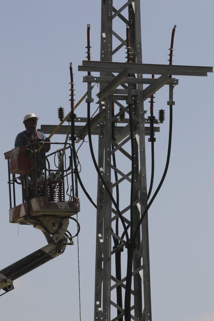 A worker of Israeli Electricity Company is raised by crane to an utility pole to perform maintenance works, in the outskirts of Jerusalem, on June 10, 2013. Photo by Flash 90 *** Local Caption *** çáøú ä çùîì òîåã çùîì òåáã îðåó òáåãä òáåãú úçæå÷ä òáåãåú úçæå÷ä àéìåñèøöéä