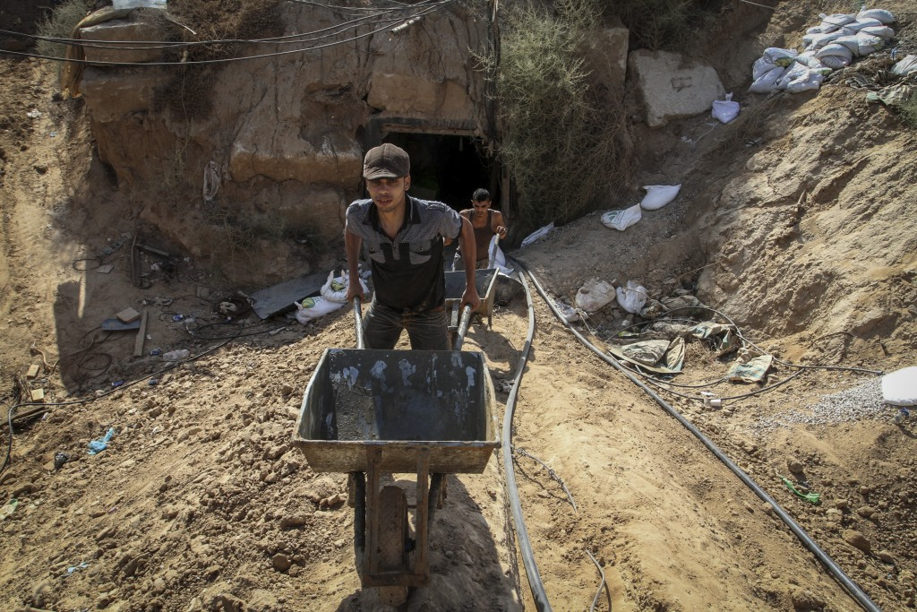 A Palestinian men work at the entrance of a tunnel, used for smuggling supplies between Egypt and the Gaza Strip, after being flooded with seawater by Egyptian army, in Rafah in southern Gaza, October 1, 2015. Last month, the Egyptian army started to pump large amounts of sea water into large pipes that have recently been extended across the border connecting Gaza and Egypt, in an attempt to destroy tunnels used to smuggle goods into the besieged coastal enclave. Photo by Abed Rahim Khatib/ Flash90 *** Local Caption *** òæä øöåòú òæä îðäøåú äáøçä äöôä îöøéí ôìñèéðéí