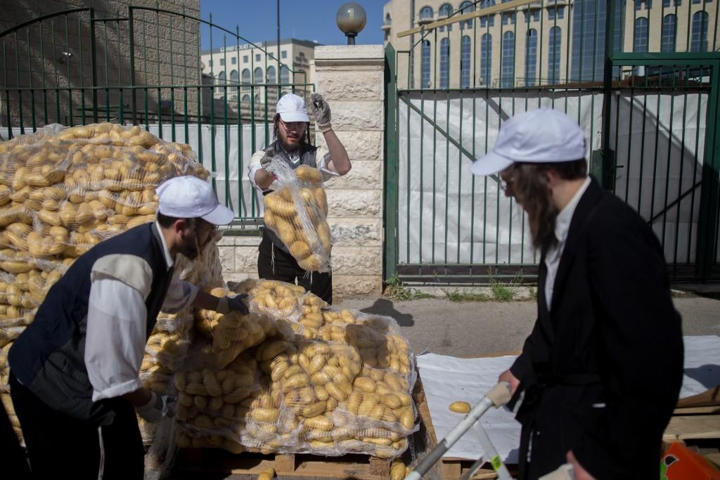 """Ultra orthodox man carry food products which is collected and then given away by Hasidic ultra orthodox, as part of the Passover customs called """"Kimcha De Pascha"""" in the ultra orthodox neighborhood of Mea Shearim, Jerusalem. April 19, 2016. Photo by Yonatan Sindel/Flash90 *** Local Caption *** çøãéí ôñç ÷îçà ãôñçà çìå÷ú îæåï îàä ùòøéí çøãéí"""
