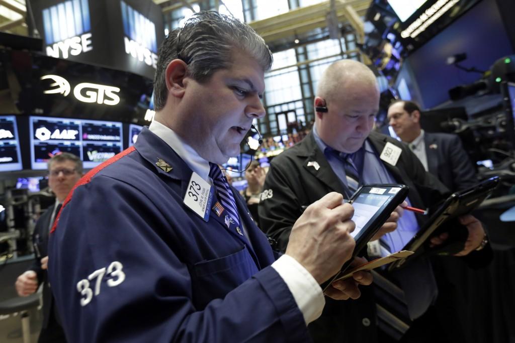 Trader John Panin, left, works on the floor of the New York Stock Exchange on Wednesday. (AP Photo/Richard Drew)