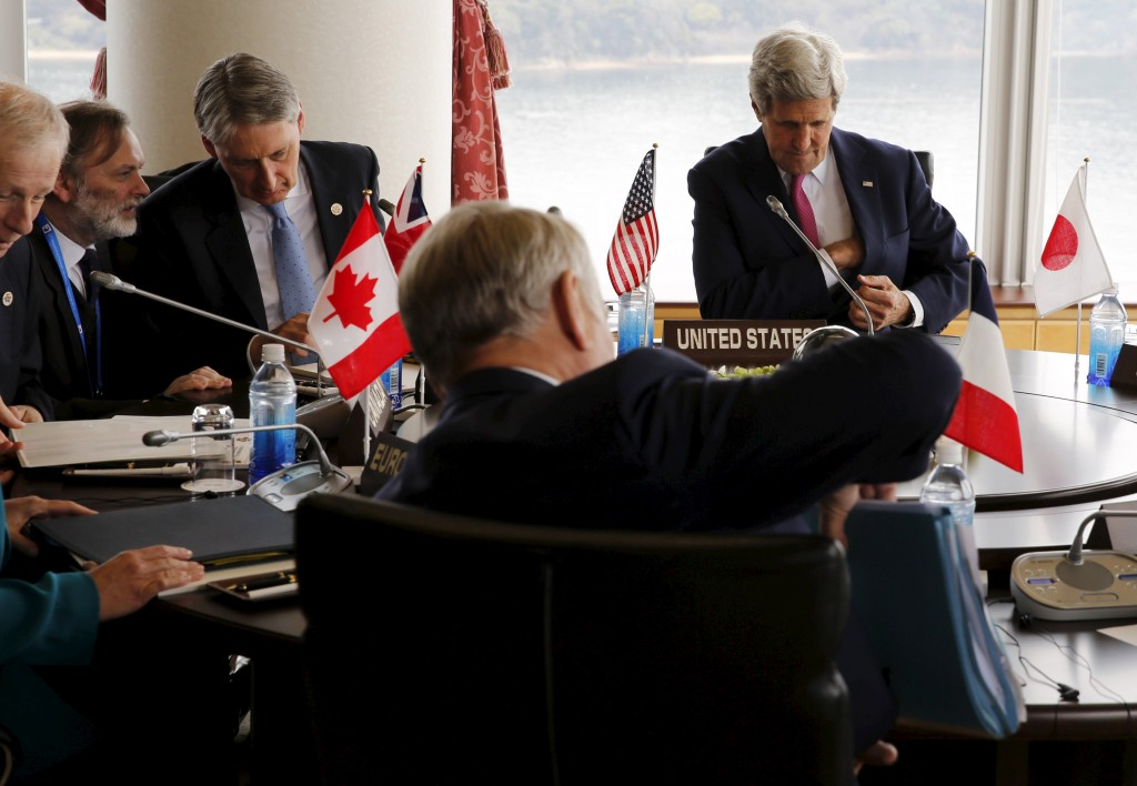 U.S. Secretary of State John Kerry (TOP R) sits with fellow top diplomats including Canada's Foreign Minister Stephane Dion (L) and Britain's Foreign Minister Philip Hammond (3rd L) as they participate in the first working session of the G7 foreign minister meetings in Hiroshima, Japan April 10, 2016. REUTERS/Jonathan Ernst