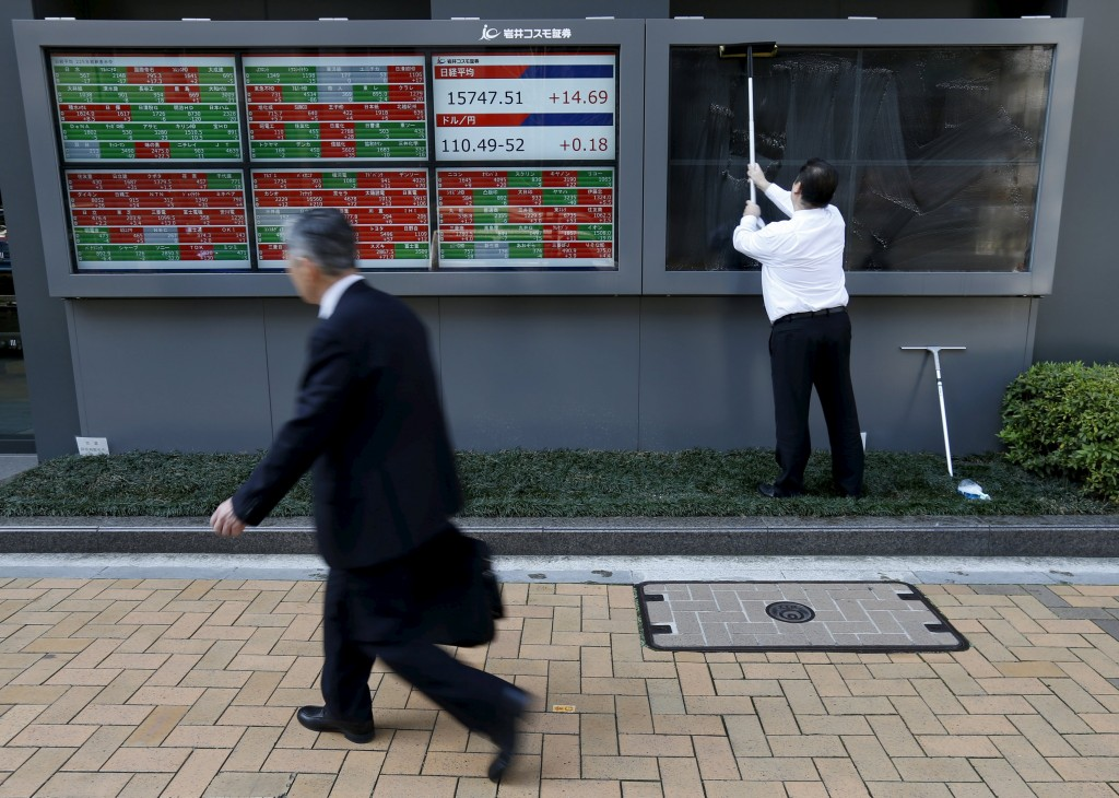 A man (R) cleans electronic boards showing the Japan's Nikkei average, the exchange rate between Japanese yen against the U.S. dollar and stock quotation outside a brokerage in Tokyo, Japan, April 6, 2016. REUTERS/Issei Kato