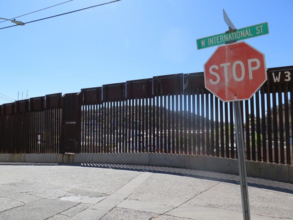 This Wednesday, March 9, 2016 photo shows a stop sign in front of the international border fence in Nogales, Ariz. Residents of this border neighborhood say presidential candidate Donald Trump's idea to build a wall between Mexico and the United States is absurd. (AP Photo/Astrid Galvan)