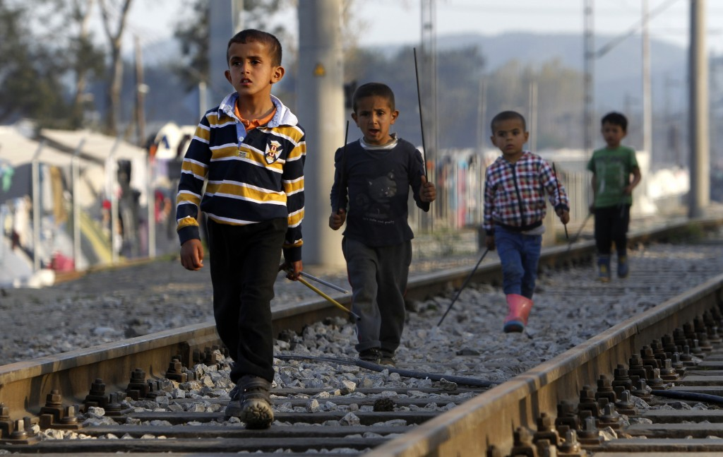 Refugee children walk along railway tracks in a makeshift camp at Idomeni border station on the Greek side of the border with Macedonia, photographed from the Macedonian side of the border line, Monday, April 4, 2016. The European plan to send migrants from Greece back to Turkey is set to be implemented starting today. (AP Photo/Boris Grdanoski)