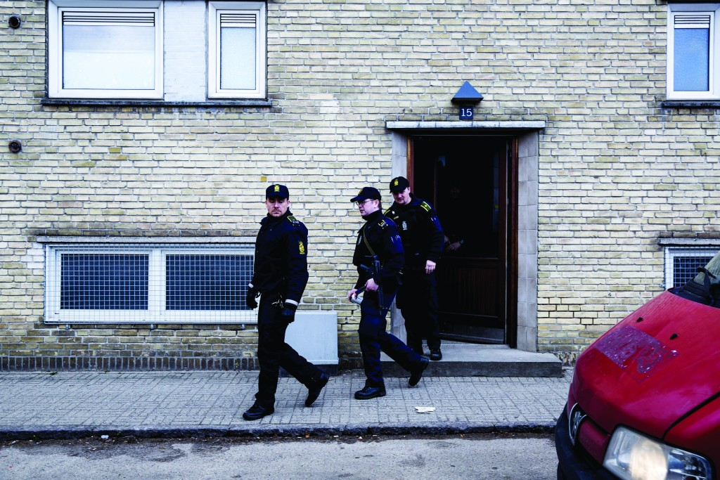 Policemen exiting an apartment block during a search for suspects believed to have travelled to Syria to join the Islamic State, in Tingbjerg, Copenhagen, April 7, 2016. (Uffe Weng/Scanpix Denmark/Reuters)