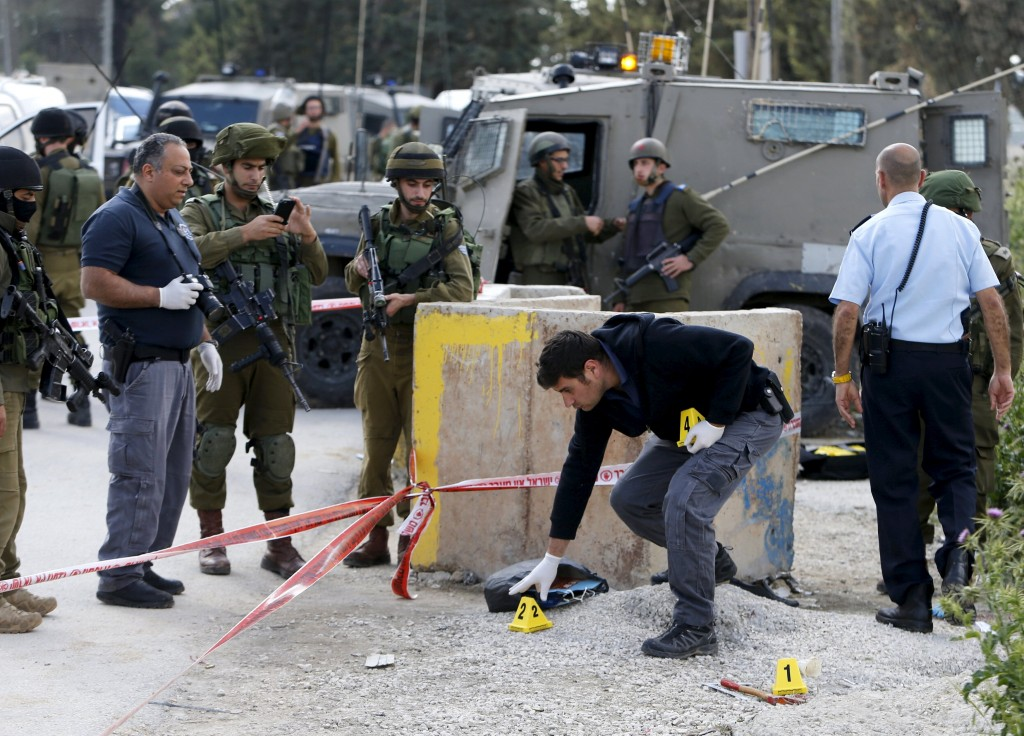 Israeli forces inspect the scene where a Palestinian, whom the Israeli military said attacked Israeli soldiers with an axe, was shot dead at the entrance of Arroub refugee camp, north of the West Bank city of Hebron April 14, 2016. REUTERS/Mussa Qawasma TPX IMAGES OF THE DAY