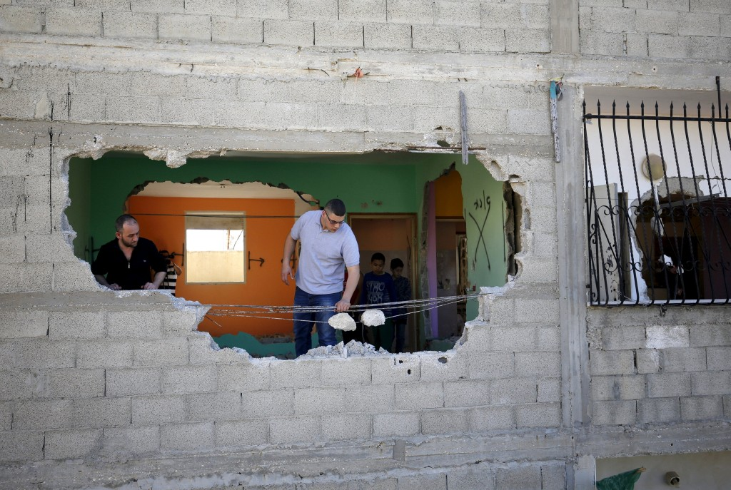 Palestinians inspect the house of Palestinian assailant Husein Abu Ghosh after it was partially destroyed by Israeli forces in Qalandia refugee camp near the West Bank city of Ramallah April 20, 2016. REUTERS/Mohamad Torokman