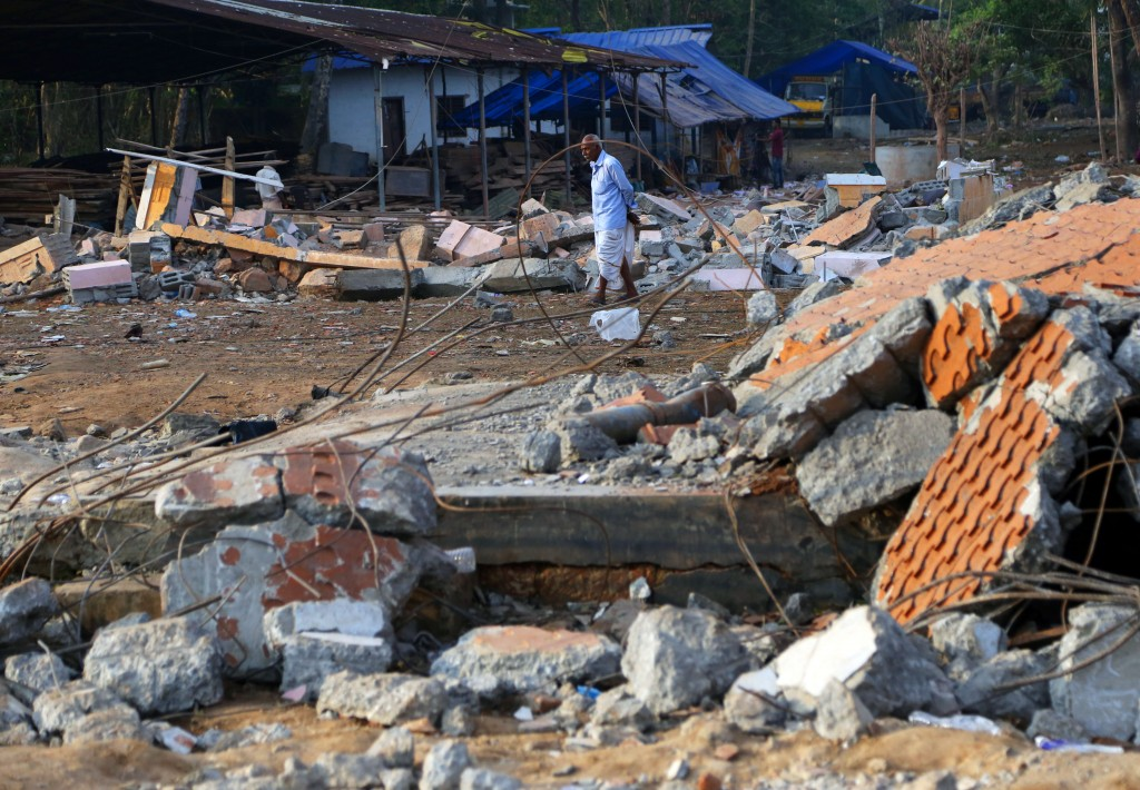 A man walks past debris from damaged structures at the spot where a massive fire broke out during a fireworks display at the Puttingal temple complex in Paravoor village, Kollam district, southern Kerala state, India, Monday, April 11, 2016. Rescue officials on Monday sifted through the Hindu temple in southern India where more than 100 died when a fireworks display - an unauthorized pyrotechnic display that went horribly wrong - swept through for a religious festival packed with thousands. (AP Photo/Aijaz Rahi)