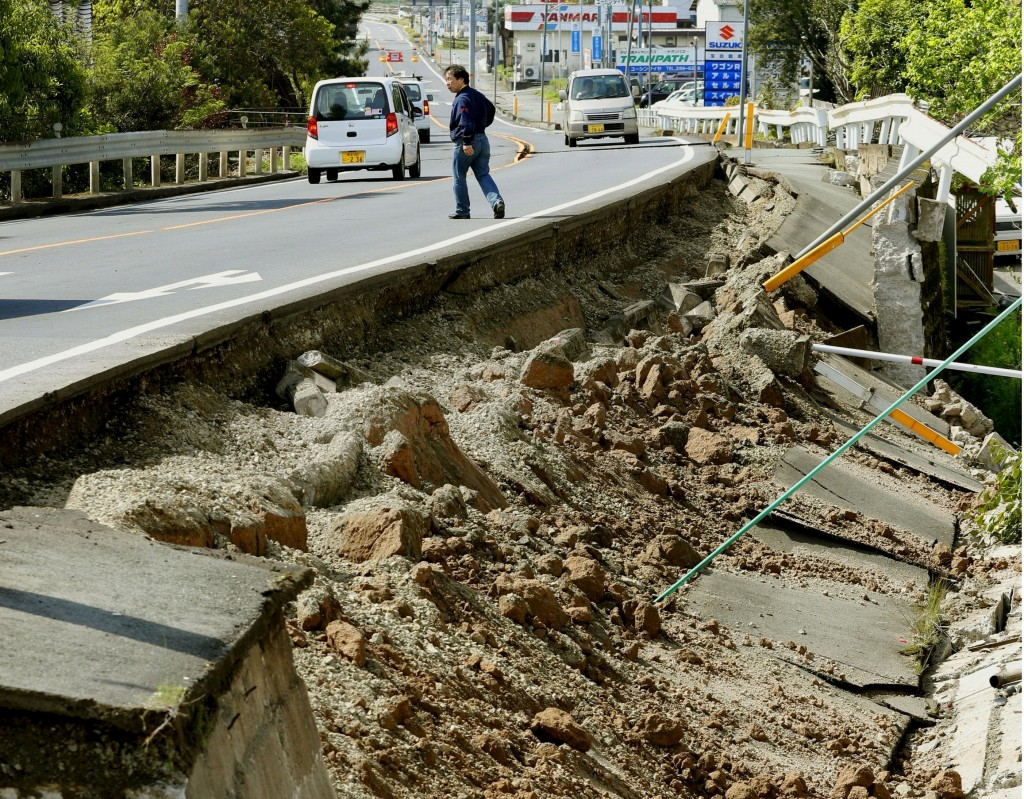 A man walks near a damaged road caused by an earthquake in Mashiki town, Kumamoto prefecture, southern Japan, in this photo taken by Kyodo April 15, 2016. Mandatory credit REUTERS/Kyodo ATTENTION EDITORS - FOR EDITORIAL USE ONLY. NOT FOR SALE FOR MARKETING OR ADVERTISING CAMPAIGNS. MANDATORY CREDIT. JAPAN OUT. NO COMMERCIAL OR EDITORIAL SALES IN JAPAN. THIS IMAGE WAS PROCESSED BY REUTERS TO ENHANCE QUALITY, AN UNPROCESSED VERSION WILL BE PROVIDED SEPARATELY.