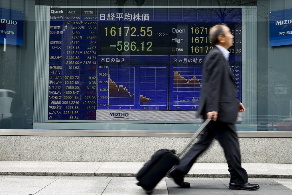 A man walks past an electronic board displaying the Nikkei average outside a brokerage in Tokyo, Japan, April 1, 2016. REUTERS/Thomas Peter
