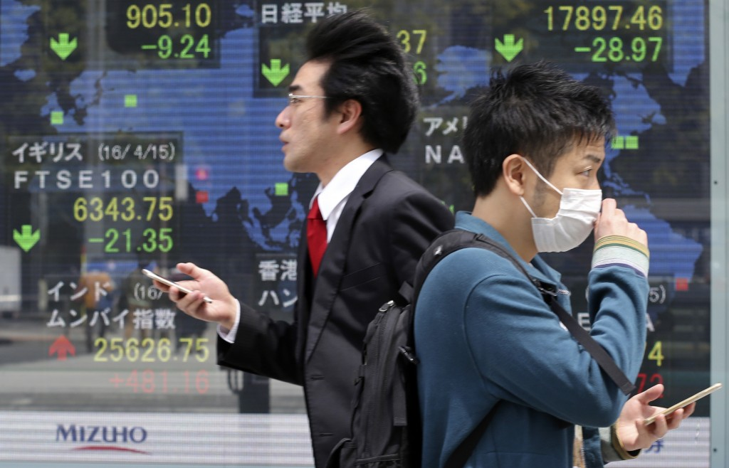 People walk by an electronic stock board of a securities firm in Tokyo, Monday, April 18, 2016. Share prices sank in early trading Monday after an effort by major oil producing nations to agree on production cuts failed over the weekend. (AP Photo/Koji Sasahara)