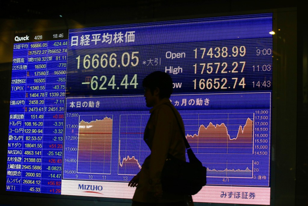 A man walks by an electronic stock indicator of a securities firm in Tokyo on Thursday. (AP Photo/Shizuo Kambayashi)