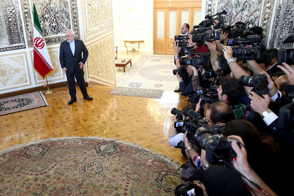 Iranian Foreign Minister Mohammad Javad Zarif stands as he waits prior to welcoming European Union foreign policy chief Federica Mogherini for their meeting in Tehran, Iran, Saturday, April 16, 2016. Iran says it will pressure the United States to ease its access to non-American banks as part of last year's landmark nuclear deal. (AP Photo/Ebrahim Noroozi)