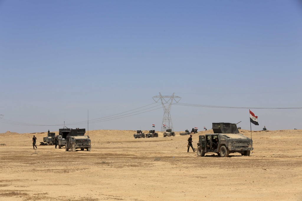 Iraq's elite counter terrorism forces advance through soft desert terrain outside the western Islamic State held town of Hit, 85 miles (140 kilometers) west of Baghdad, Iraq, Sunday, April 3, 2016. Iraqi forces said Sunday that they have taken the northern edge of the Islamic State group held town of Hit, after hundreds of roadside bombs littering the surrounding area slowed progress for days. (AP Photo/Khalid Mohammed)