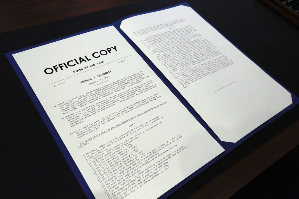 The official copy of New York State's $15 minimum wage bill is displayed at the Jacob Javits Center, Monday, April 4, 2016,in New York. Gov. Andrew Cuomo is scheduled to sign the bill Monday. On Friday, the New York Legislature passed a plan that would gradually raise the minimum wage to $15 in New York City by the end of 2018 and in some prosperous suburbs by the end of 2021. The minimum wage would only rise to $12.50 in the rest of the state by 2020, with further increases tied to inflation and other economic indicators. (AP Photo/Richard Drew, Pool)