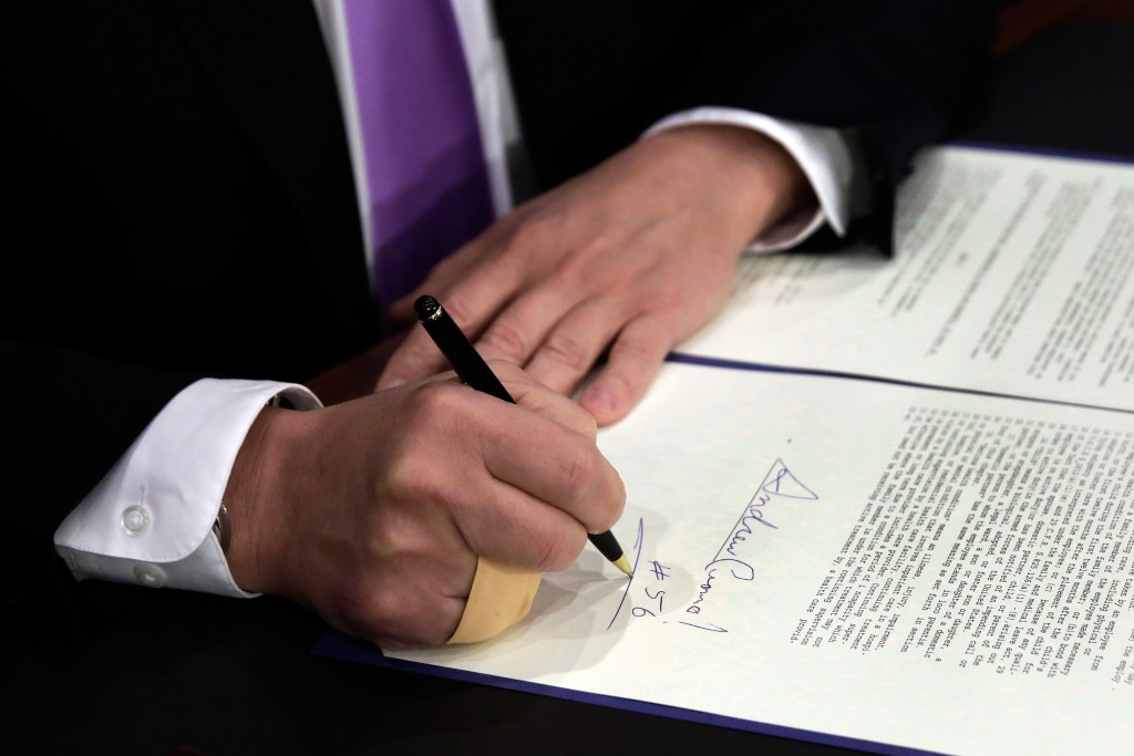 New York Gov. Andrew Cuomo signs the new minimum-wage law at the Javits Convention Center in Manhattan on Monday. (AP Photo/Richard Drew, Pool)