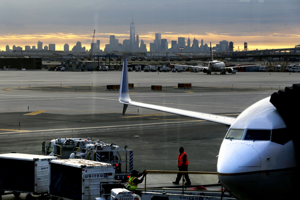 FILE - In a May 1, 2015 file photo, a United Airlines employee walks near a jet parked at Terminal C of Newark Liberty International Airport as the sun rises behind the New York City skyline, in Newark, N.J. The Federal Aviation Administration announced Friday, April 1, 2016, that it is easing limits on the number of hourly flights at Newark Liberty International Airport, and the airport's operator said that should lead to greater competition and lower fares.(AP Photo/Julio Cortez, File)