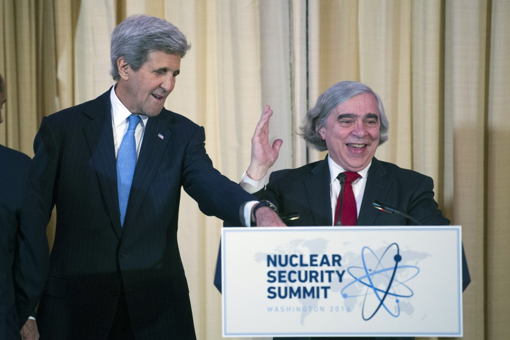 Secretary of State John Kerry, left, adjusts a microphone for Energy Secretary Ernest Moniz as they make remarks at the top of a State Department dinner for Nuclear Security Summit delegation guests, in Washington, Thursday, March 31, 2016. (AP Photo/Cliff Owen)