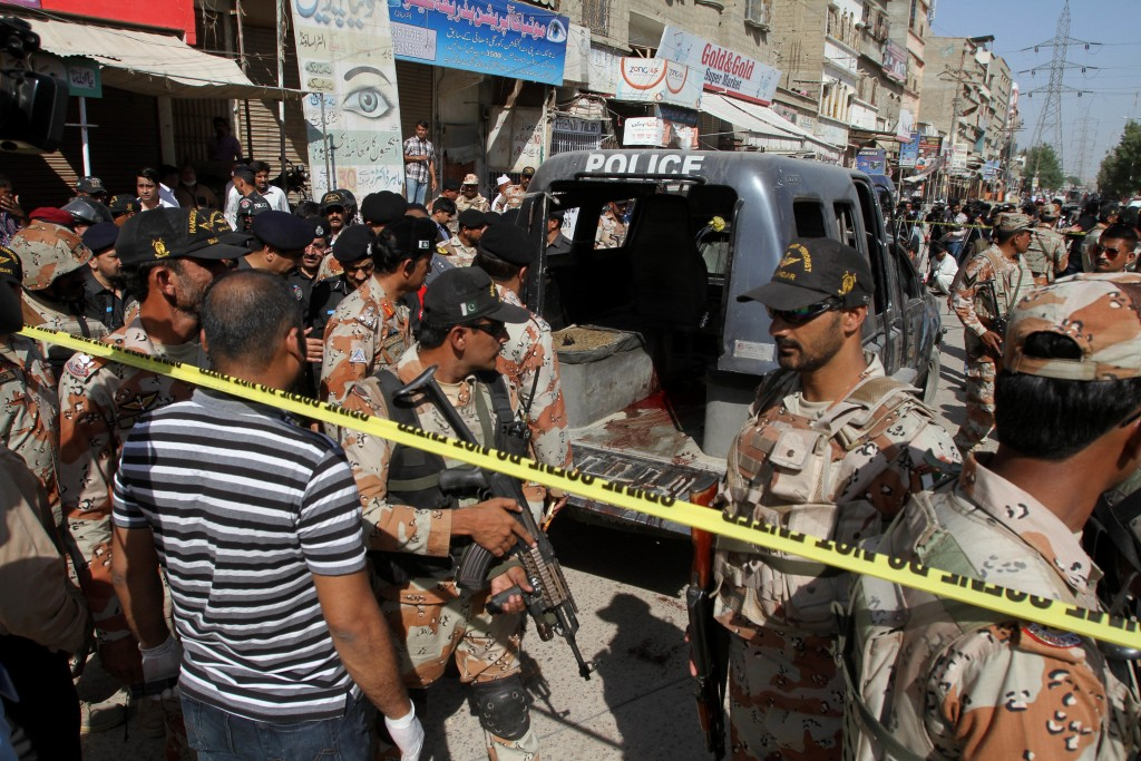 Soldiers of a Pakistani para military force cordon off the area and police vehicle, attacked by gunmen in Karachi, Pakistan, Wednesday The slain police officers had been deployed to protect health workers administering polio vaccinations.  (AP Photo/Fareed Khan)