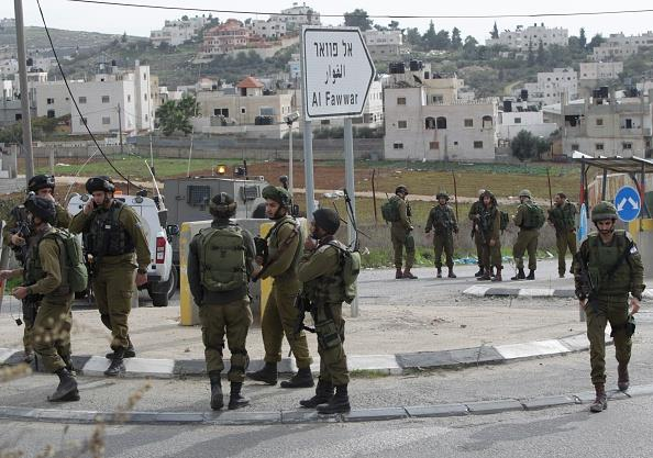 Israeli soldiers gather at the site of a stabbing attack at the Al-Fawwar junction near the city of Chevron on Wednesday, the site of a stabbing attack. (HAZEM BADER/AFP/Getty Images)