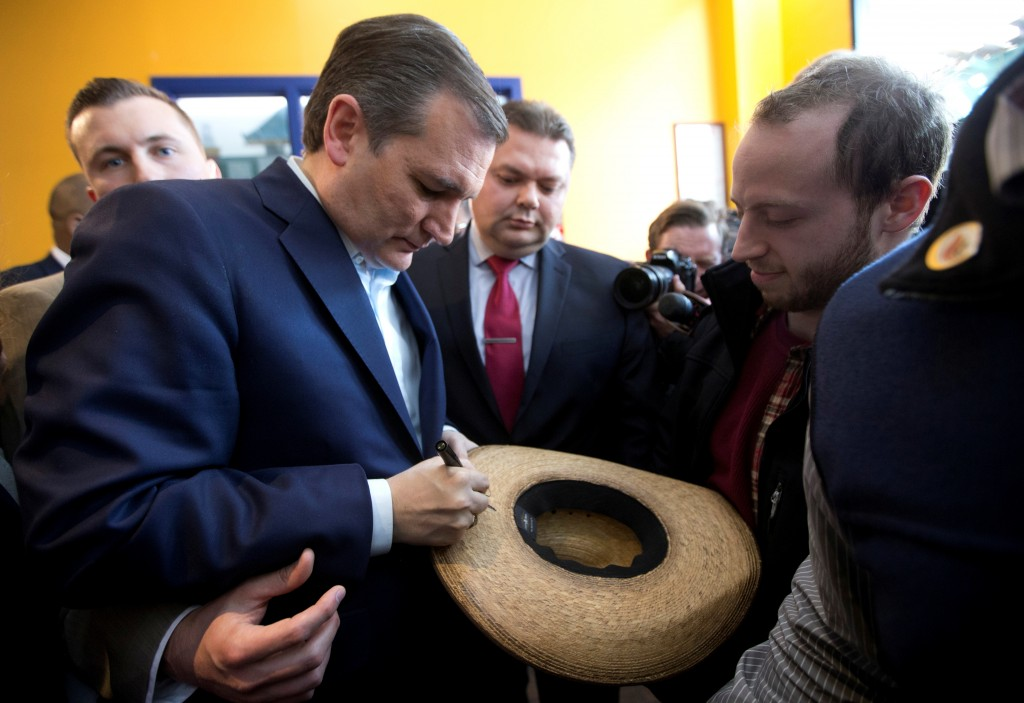 Republican presidential candidate Sen. Ted Cruz on Wednesday autographs a hat at a Bronx restaurant as the presidential campaign rolls into New York. (AP Photo/Mary Altaffer)