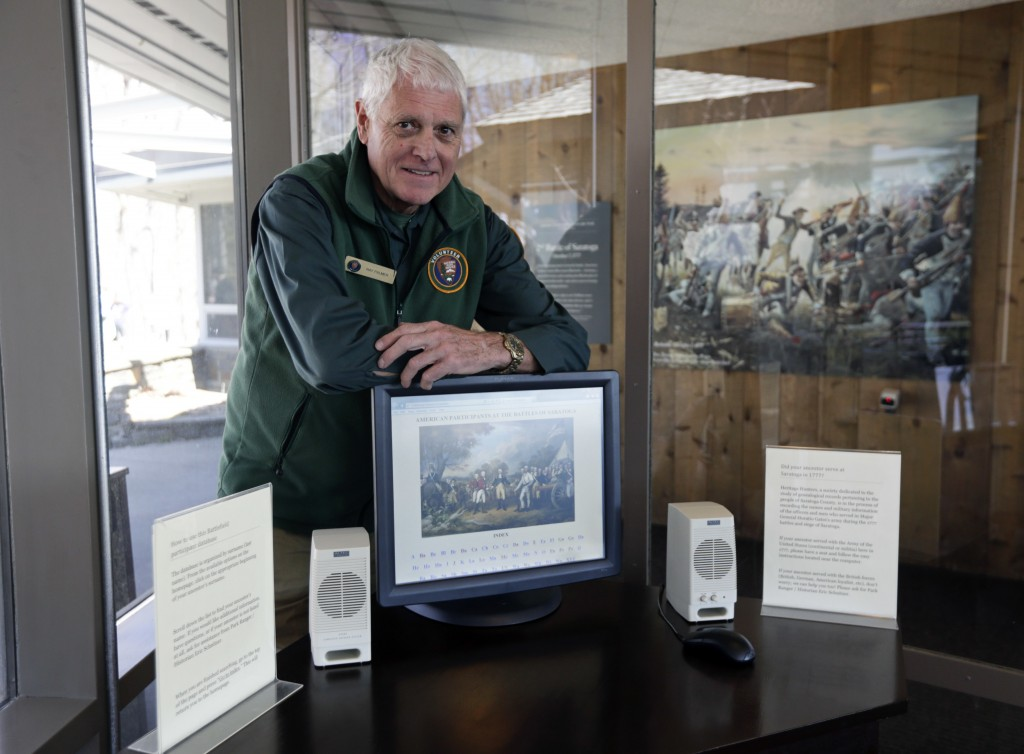 Volunteer Ray Palmer poses with a computer used to search the genealogy of the American soldiers who fought the British and their German allies in the two Saratoga battles at Saratoga National Historical Park in Stillwater, N.Y. (AP Photo/Mike Groll)