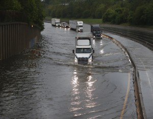 Trucks slowly drive through flood waters on North I-45  as White Oak Bayou comes over its banks on Monday. (Karen Warren/Houston Chronicle via AP)