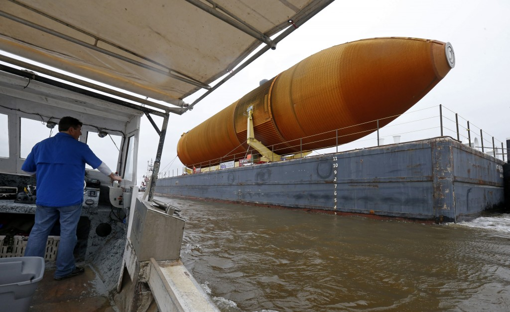 In this Tuesday, April 12, 2016 photo, external Tank, ET- 94, NASA's only remaining space shuttle external tank, is transported by tug and barge down the Intracoastal Waterway from the NASA Michoud Assembly Facility in New Orleans. The tank is embarking on a journey, via the Gulf of Mexico and the Panama Canal, to the California Science Center in Los Angeles, as part of the Space Shuttle Endeavour display. (AP Photo/Gerald Herbert)